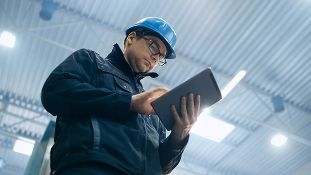 Factory worker in a hard hat is using a tablet computer